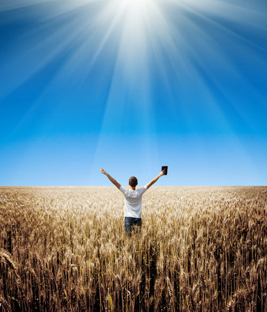 man holding up Bible in a wheat field