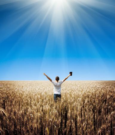Mężczyzna trzyma Biblię w polu pszenicy