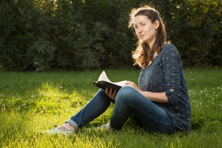 field study: Teen girl reading the Bible sitting outdoors