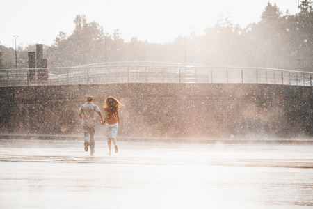 The girl with the boy run under a downpour rain Stockfoto