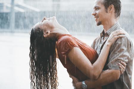 Het meisje met de jongen draait onder een stortbui regen
