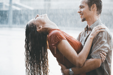 love in rain: The girl with the boy run under a downpour rain Stock Photo