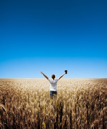 bibles: man holding up Bible in a wheat field