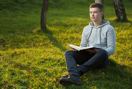 Young man reading Bible in a park 스톡 콘텐츠