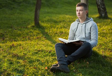 bible ouverte: Jeune homme lecture de la Bible dans un parc Banque d'images
