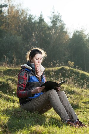 field study: Teen girl reading the Bible outdoors at sunset time