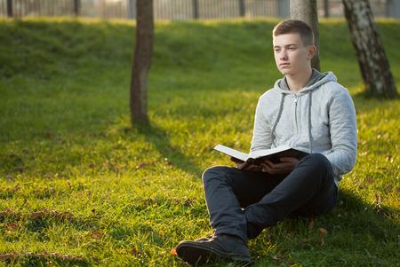 leer biblia: Hombre joven que lee la Biblia en un parque