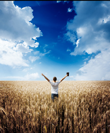spiritual background: man holding up Bible in a wheat field
