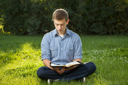 bible open: Young man reading Bible in a park Stock Photo