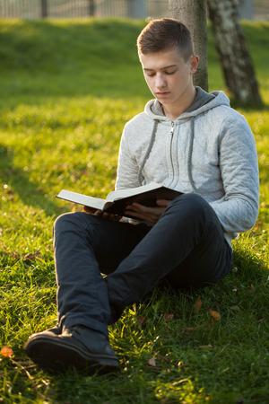公園では、聖書を読んでいる若い男の人