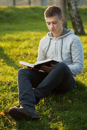 Young man reading Bible in a park Banque d'images