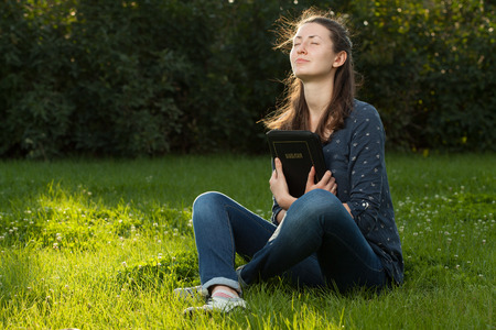 Teen girl gugging the Bible sitting outdoors with copy space
