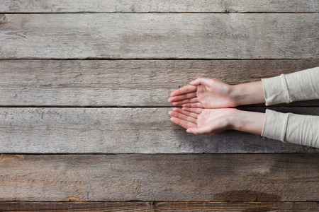 open concept: woman hands with open palms over wooden table Stock Photo