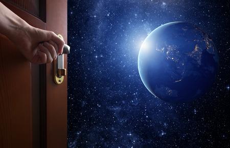 Hand öffnet leeren Raum Tür zu Planet Erde aus dem Weltraum. Standard-Bild