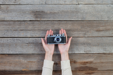 color digital camera: Hand holding a retro camera over wooden table Stock Photo