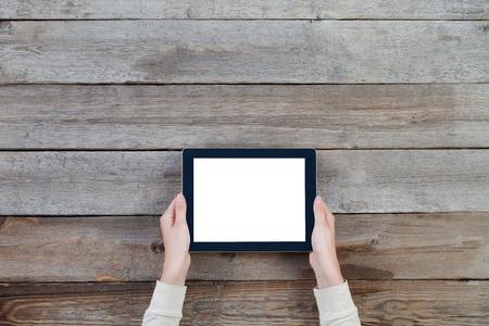 vrouwelijke handen die digitale tablet computer met geïsoleerde scherm over oude grijze houten achtergrond tafel.