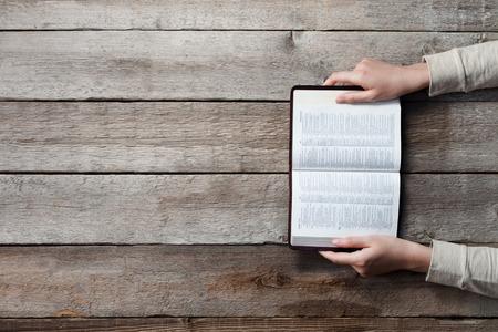 žena ruce na Bibli. ona čte a modlí se nad Biblí přes dřevěný stůl