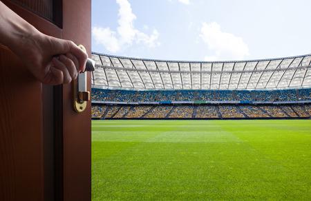 campo calcio: mano apre porta della stanza a campo di calcio Archivio Fotografico