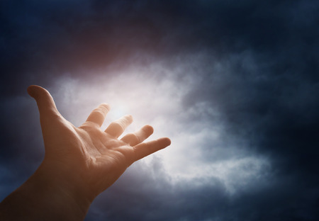 Hand reaching for the  sky with dark stormy clouds