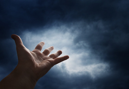 man arm: Hand reaching for the  sky with dark stormy clouds