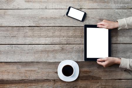 manos femeninas celebración de ordenador tableta digital con pantalla aislado más vieja mesa de madera de fondo gris.
