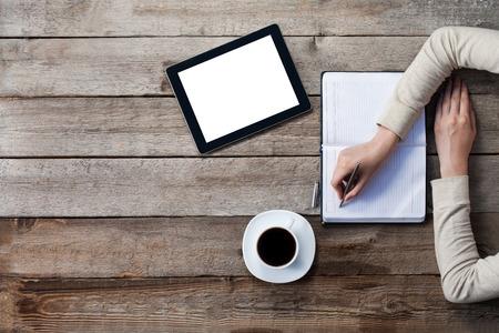 Frau schreibt auf einem Papier mit Bildschirm des digitalen Tablette neben ihr. Top Winkel Standard-Bild