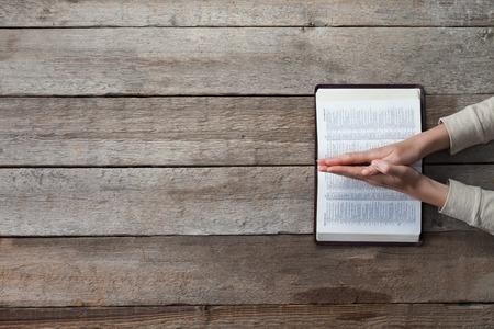 biblia: manos de la mujer en la biblia. que está leyendo y orando sobre la biblia sobre la mesa de madera