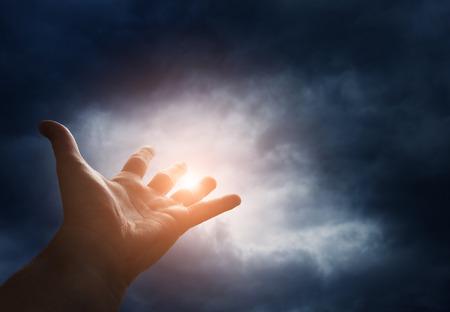 mano de dios: Mano que alcanza para el cielo con nubes oscuras de tormenta