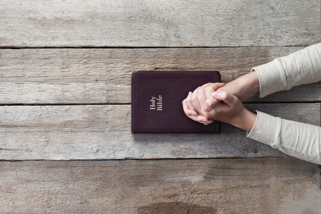woman hands on bible. she is reading and praying over bible over wooden table Archivio Fotografico