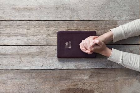 vrouw handen op bijbel. Ze is het lezen en bidden over Bijbel over houten tafel