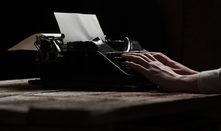 writers block: Hands writing on old typewriter over wooden table background