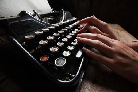 the typewriter: Manos que escriben en la vieja m�quina de escribir sobre fondo mesa de madera