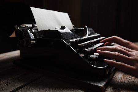 schreiben: Hände schriftlich auf alte Schreibmaschine über Holztisch Hintergrund
