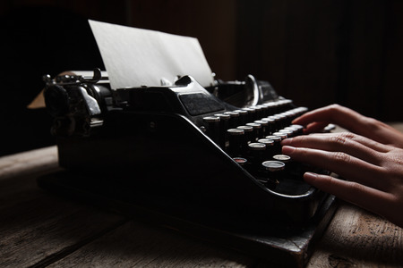 write: Hands writing on old typewriter over wooden table background