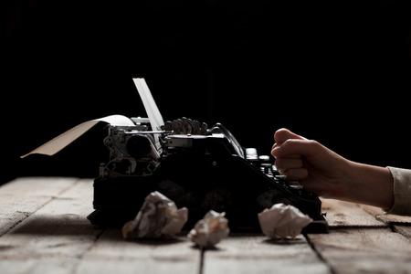maquina de escribir: Manos que escriben en la vieja máquina de escribir sobre fondo mesa de madera