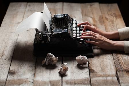 napsat: Ruce psaní na starý psací stroj přes dřevěný stůl pozadí