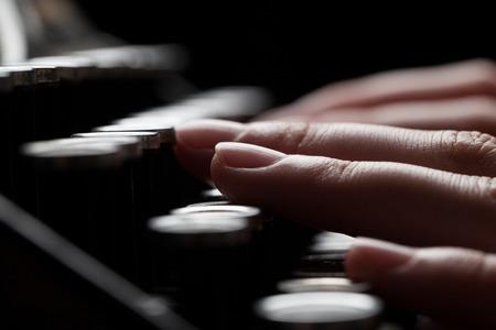 maquina de escribir: escritura dedo en vieja máquina de escribir sobre fondo mesa de madera