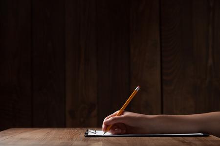 escritura: Escritura de la mano de la mujer en el papel sobre la mesa de madera