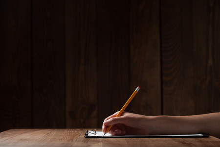 womans hand writing on paper over wooden table