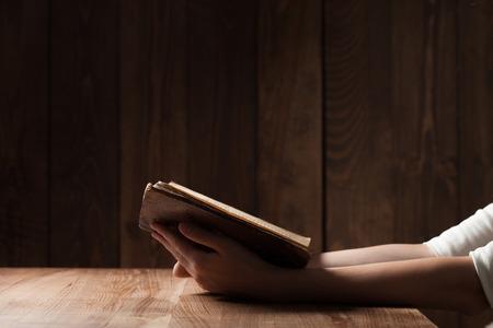 pardon: femme lisant la Bible dans l'obscurit� sur la table en bois