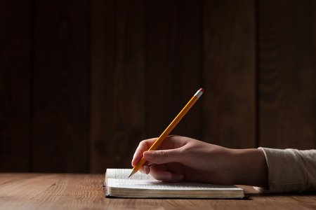 writing paper: womans hand writing on paper over wooden table