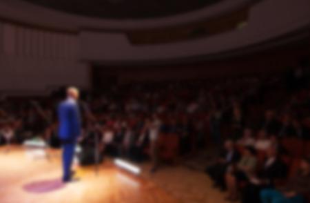 wazig beeld van een zakenman het geven van een presentatie in een conferentie  vergadering