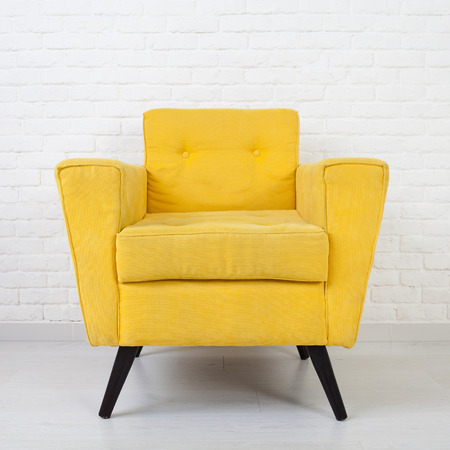 elbow chair: White wall texture with a retro yellow armchair