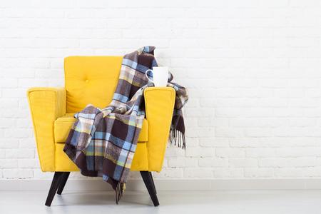 レトロな黄色の肘掛け椅子と白い壁のテクスチャ 写真素材