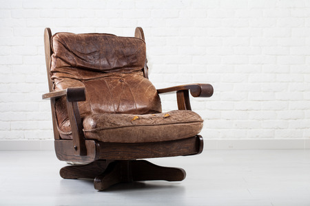 classic interior: retro leather brown armchair next to a white wall Stock Photo