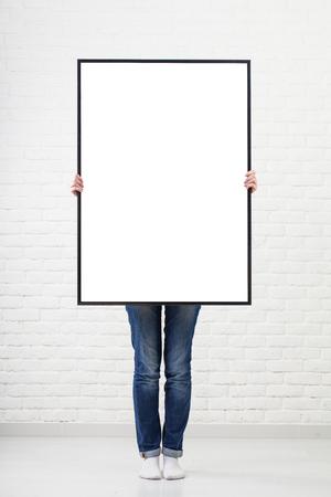 hoja en blanco: mujer con el cartel en blanco sobre fondo de pared Foto de archivo