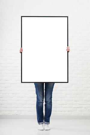 man holding card: woman with blank poster on wall background