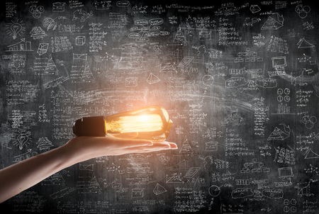 creative industries: hand holding or showing a light bulb in front of business idea concept on wall backboard blackground