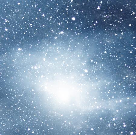 劇的な暗い空の青い背景に雪が降る