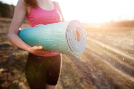 mat: woman walking with a yoga mat outside during sunset n a rural area wearing sports wear and doing yoga Stock Photo